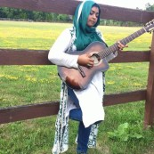 Tazeen Ayub plays guitar in front of a a wood fence. A field with flowers is in the background.